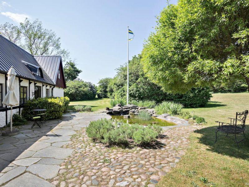 Henriksdals gård uteplats med fruktträd, grönytor och guldfiskdamm